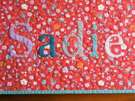 Hand appliquéd name on whole cloth baby quilt by Organic Quilt Company