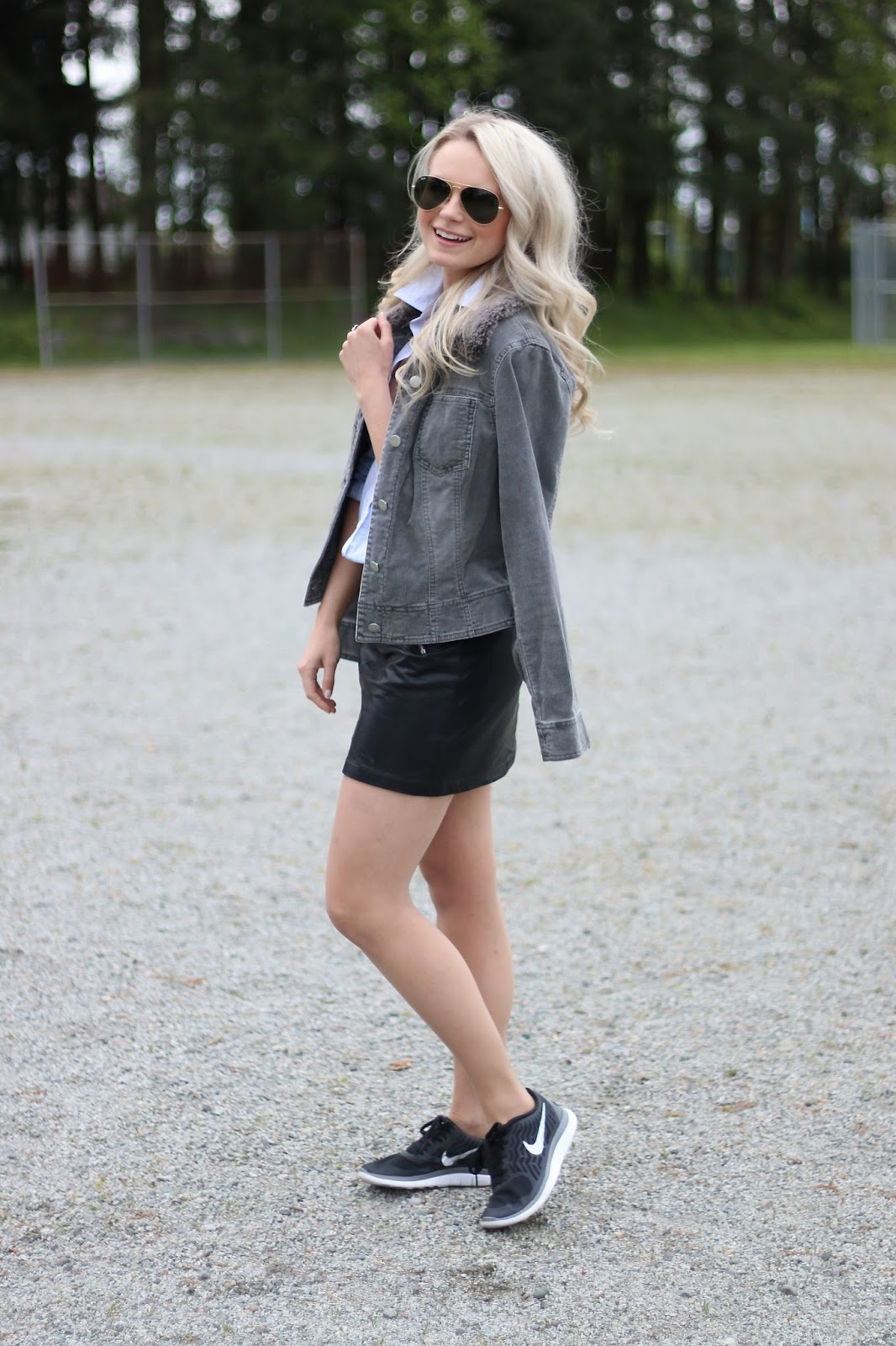 a fashion blogger models neutral fall fashions with a vintage denim jacket and nike shoes