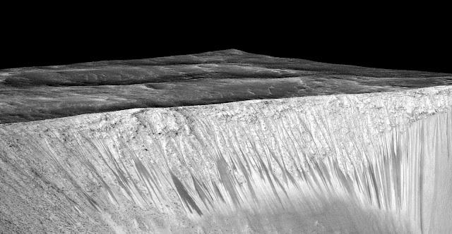 Những vệt tối hẹp và xuất hiện định kỳ hay RSL bắt nguồn từ những miệng núi lửa. Trong hình là miệng núi lửa Garni được chụp bởi Tàu Thăm dò Quỹ đạo Hỏa Tinh (MRO). Những RSL này dài tới hàng trăm mét, và được cho là hình thành bởi những dòng chảy nước mặn. Hình ảnh bởi NASA/JPL/Đại học Arizona.