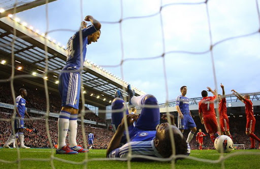 Chelsea's Michael Essien lies on the ground after failing to stop a goal from Liverpool's Daniel Agger