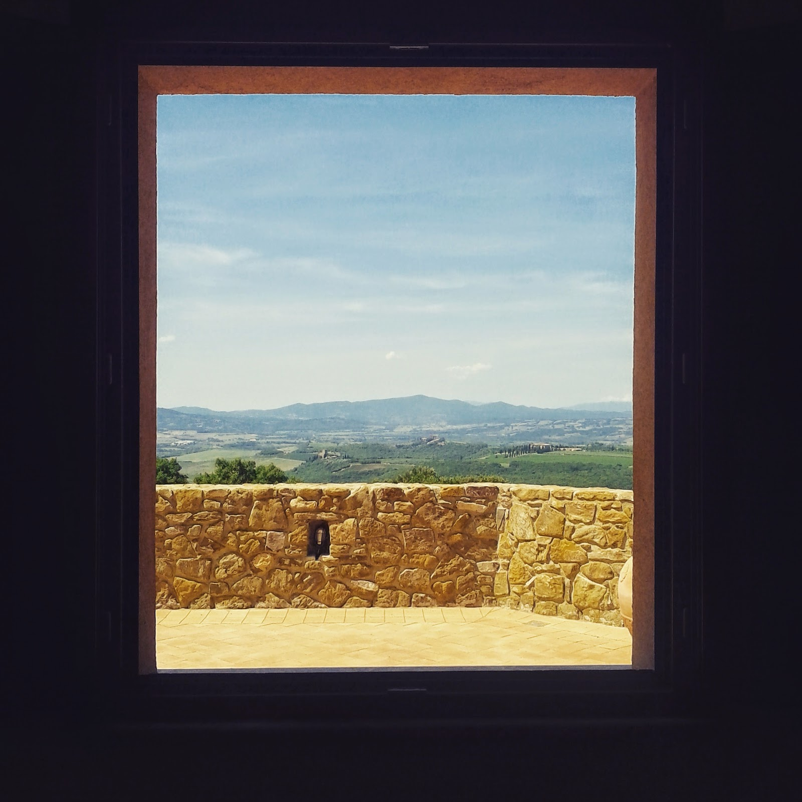 The Tuscan landscaped seen through the window of a winery