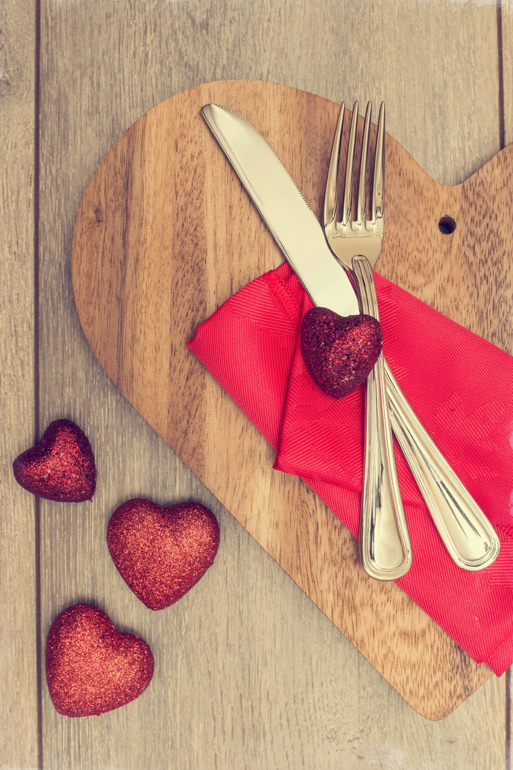 Utensils and hearts on cutting board and table