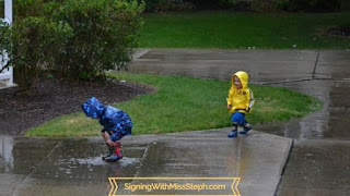 Boys splashing in puddles wearing rain coats and rain boots