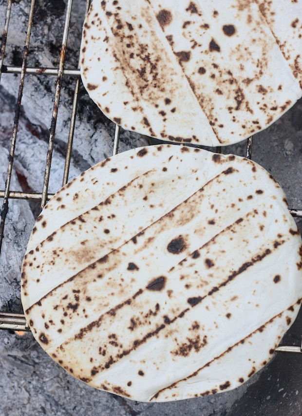 Naan bread cooking on campfire grill