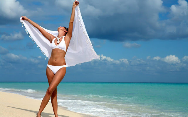 Vrouw in witte bikini op het strand
