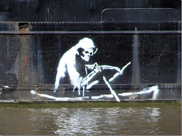 Banksy's version of the Silent Highwayman (1858) stenciled in white on the side of The Thekla in Bristol, UK just above the water line (April 2005)