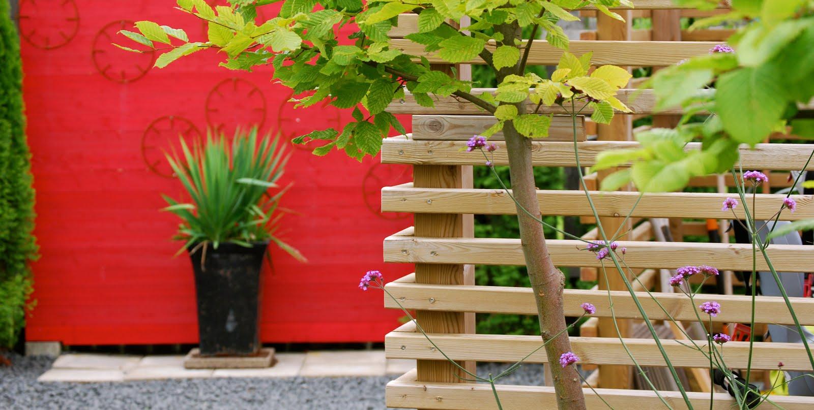 För att lätta upp ett trist staket har en röd skärmvägg byggts.