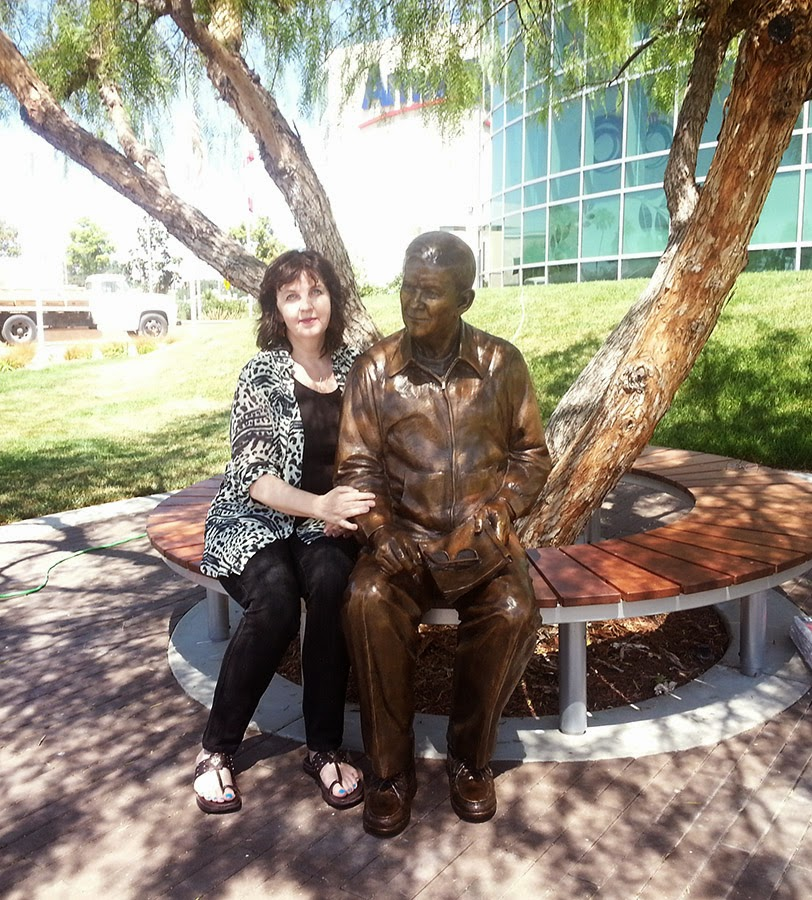 Sculptor Lena Toritch posing with custom bronze portrait statue