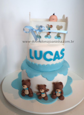 Bolo chá de bebê com o bebê no bercinho, nome na lateral do bolo e decorado com família de ursinhos marrom, detalhes em branco e azul.