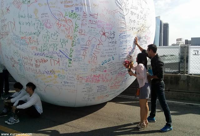Coreanos escribiendo mensajes en una gran pelota blanca