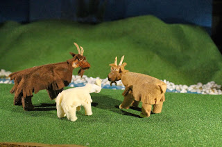 Photograph of three finished goat models on grassy set.
