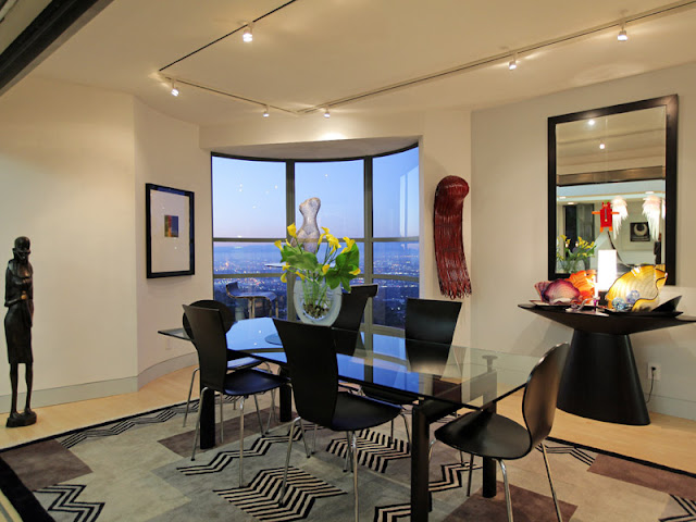Photo of modern dining room interiors with glass table and black chairs