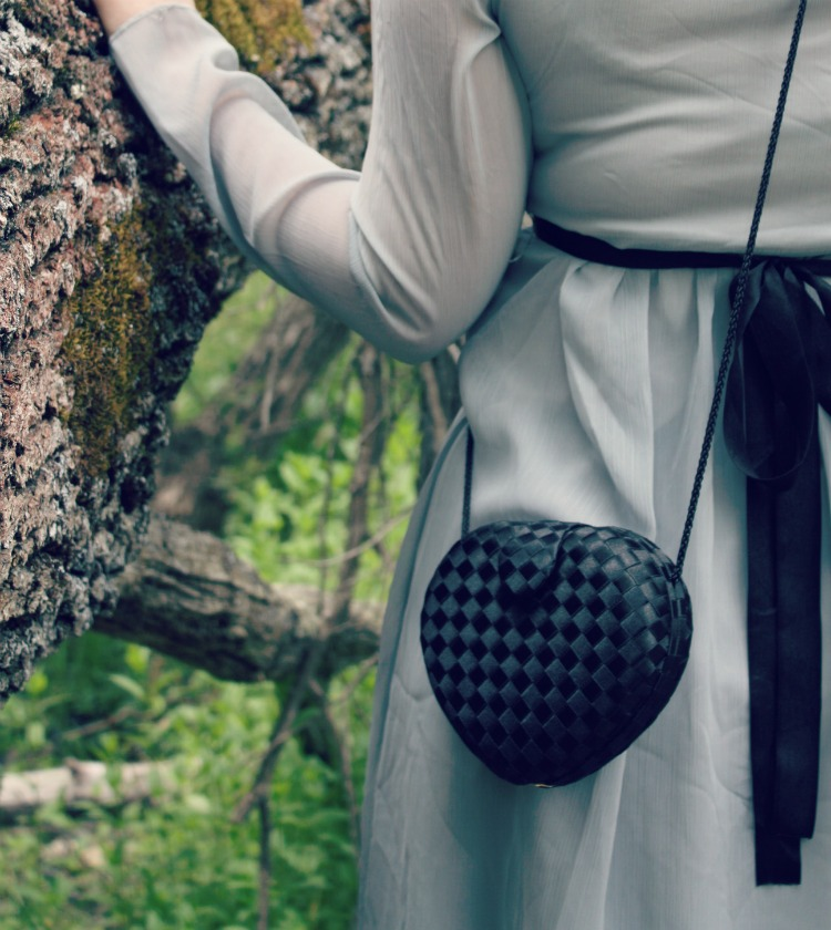 girl in grey dress bow in the woods black vintage heart shaped purse
