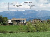La gran masia de Can Serrabou en primer terme i lluny al seu darrere les Serres de Curull i de Bellmunt