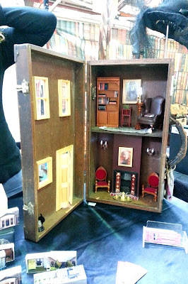 Dolls' house in a suitcase on a market stall.