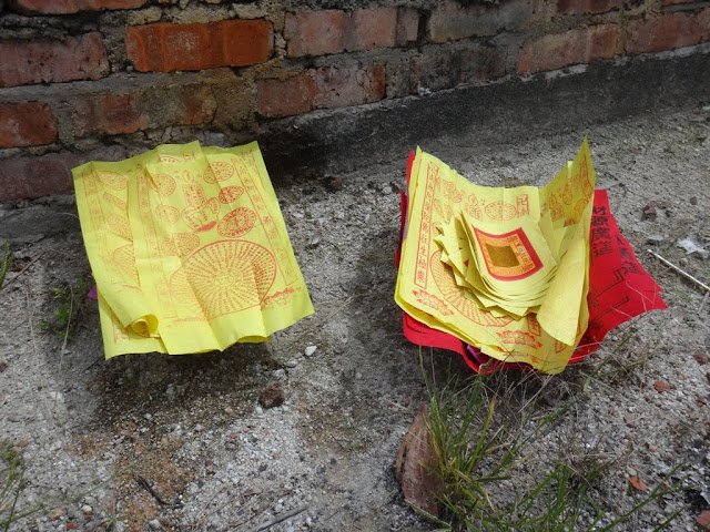 Some of joss paper are arranged accordingly and ready to be burned as an offering to ancestors or the loved ones in front of their tombs at Chinese cemetery in Malaysia