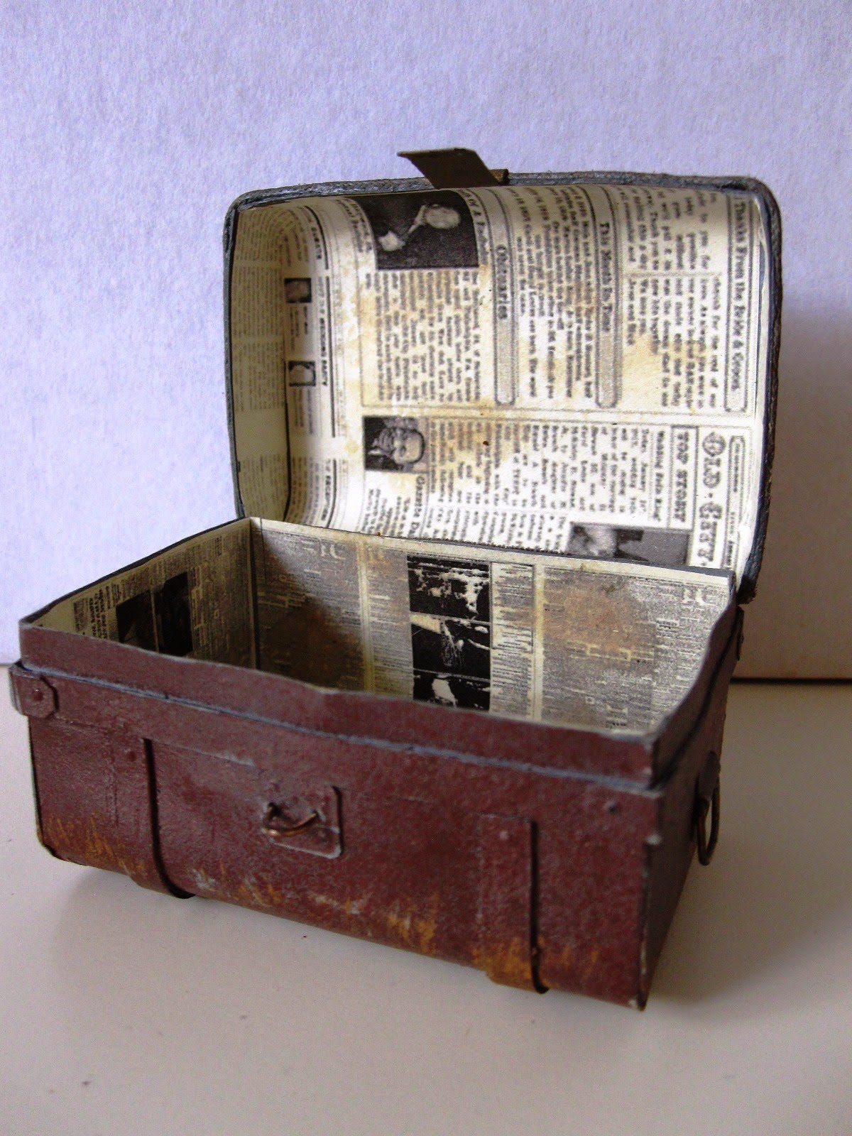 Open miniature vintage tin trunk, showing newspaper lining.