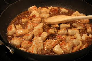 adding sesame sauce to chicken in skillet