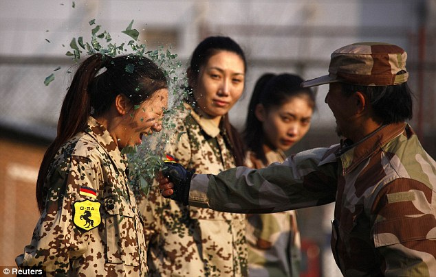Extreme methods: An instructor smashes a bottle over a female recruit's head during a training session for China's first female bodyguards in Beijing