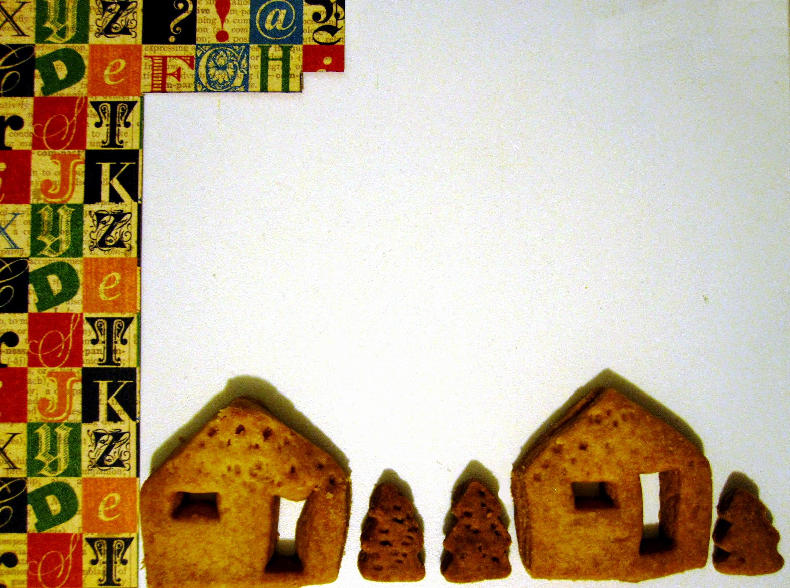 Part of a piece of scrapbooking paper with a typographic design next two several shortbread biscuits in the shape of houses and trees.