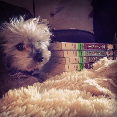 Murchie regards the camera with a long-suffering look on his face. Beside him is a pile of Death Note with only their spines visible.