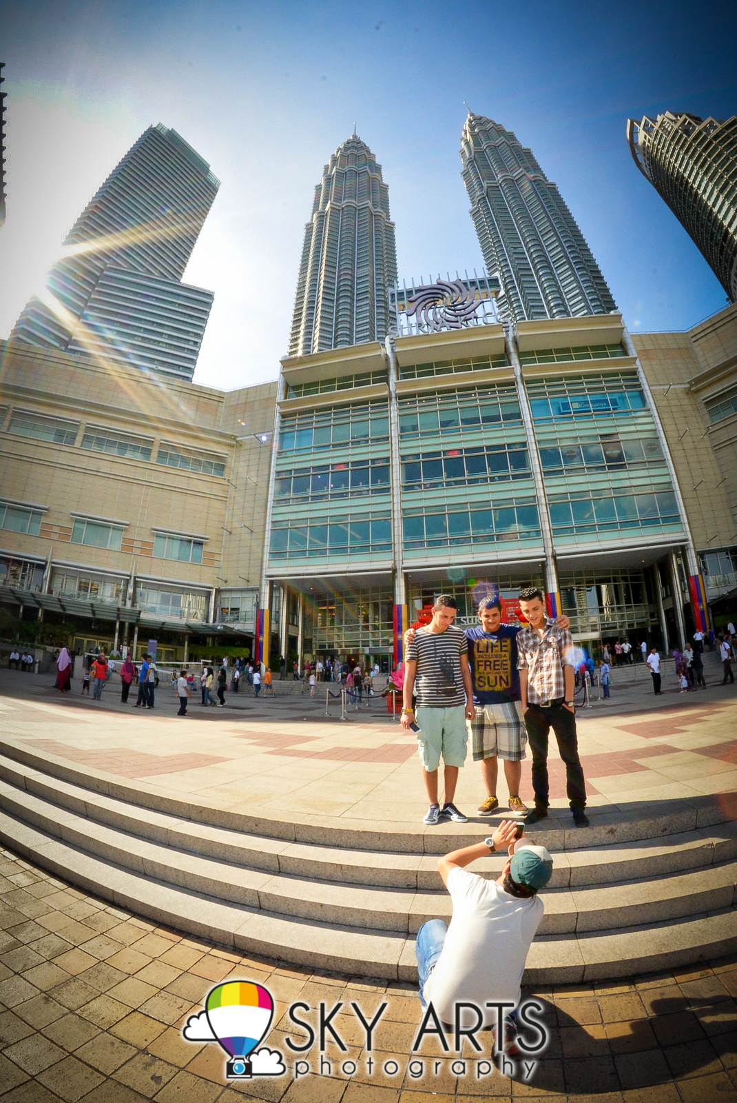 The tourists were standing at the exact spot where you can get a  proportional shoot of the two cute PETRONAS twin towers. The weather was  hot but it was ...