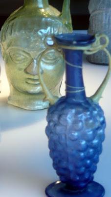 vasijas de vidrio coloreado, la una con forma de cabeza humana y la otra en forma de racimo