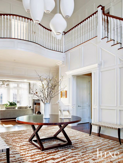 luxe two story foyer white wainscoting wall paneling