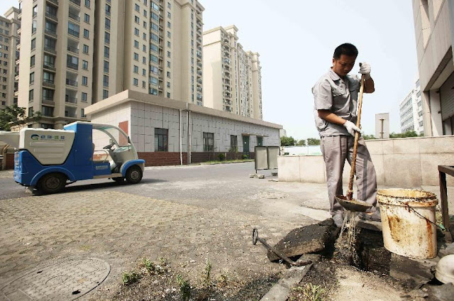 Man extracting gutter oil from the sewer