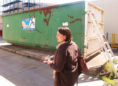A woman walking past a large rubbish skip.