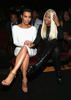 Kim Kardashian and Nicki Minaj sitting in their seats and posing for cameras at the 2012 BET Awards