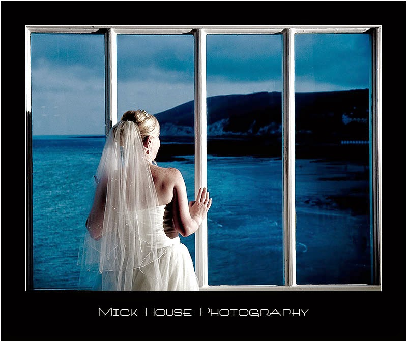 Bride looking through a window at the Ocean Suite, Eastbourne