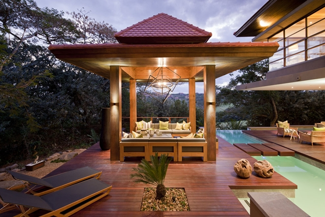 Shaded terrace surrounded by the pool at Contemporary South African SGNW House by Metropole Architects at night