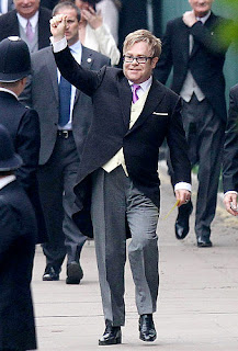 Elton John, a close personal friend of the late Princess Diana, waves as he enters the Abbey