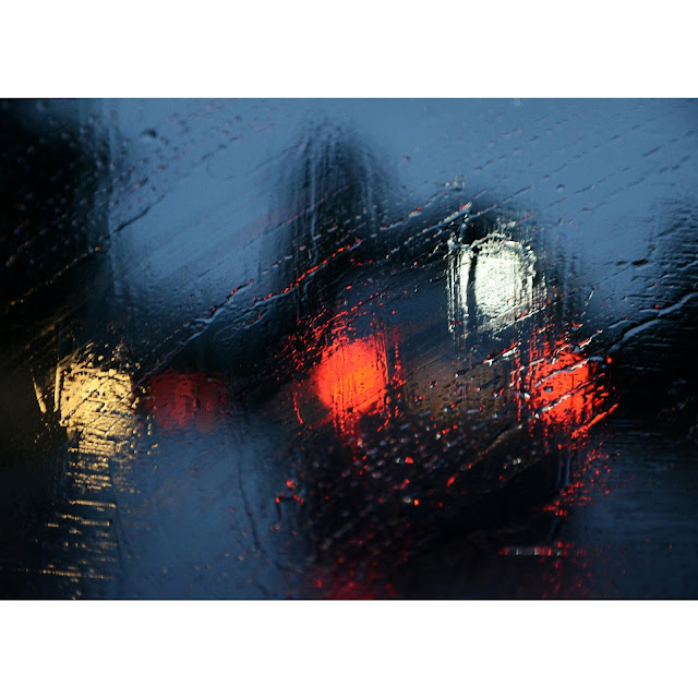 Windows with raindrops and streaks of water to see foggy headlights on a long drive in the monsoons