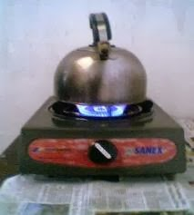 memanaskan air dengan kompor cara tradisional untuk mandi hangat