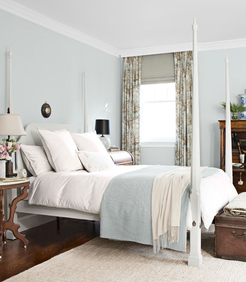 light blue and white bedroom with a four poster bed, floral curtains, a trunk at the foot of the bed, wood floor and a sisal rug