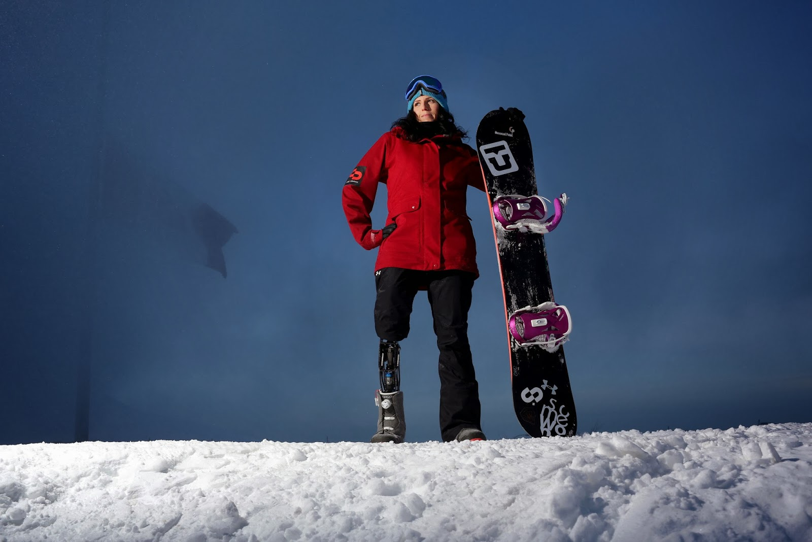 picture of michelle in snow with her snowboard. She is a right leg amputee and is wearing a prostetic leg.
