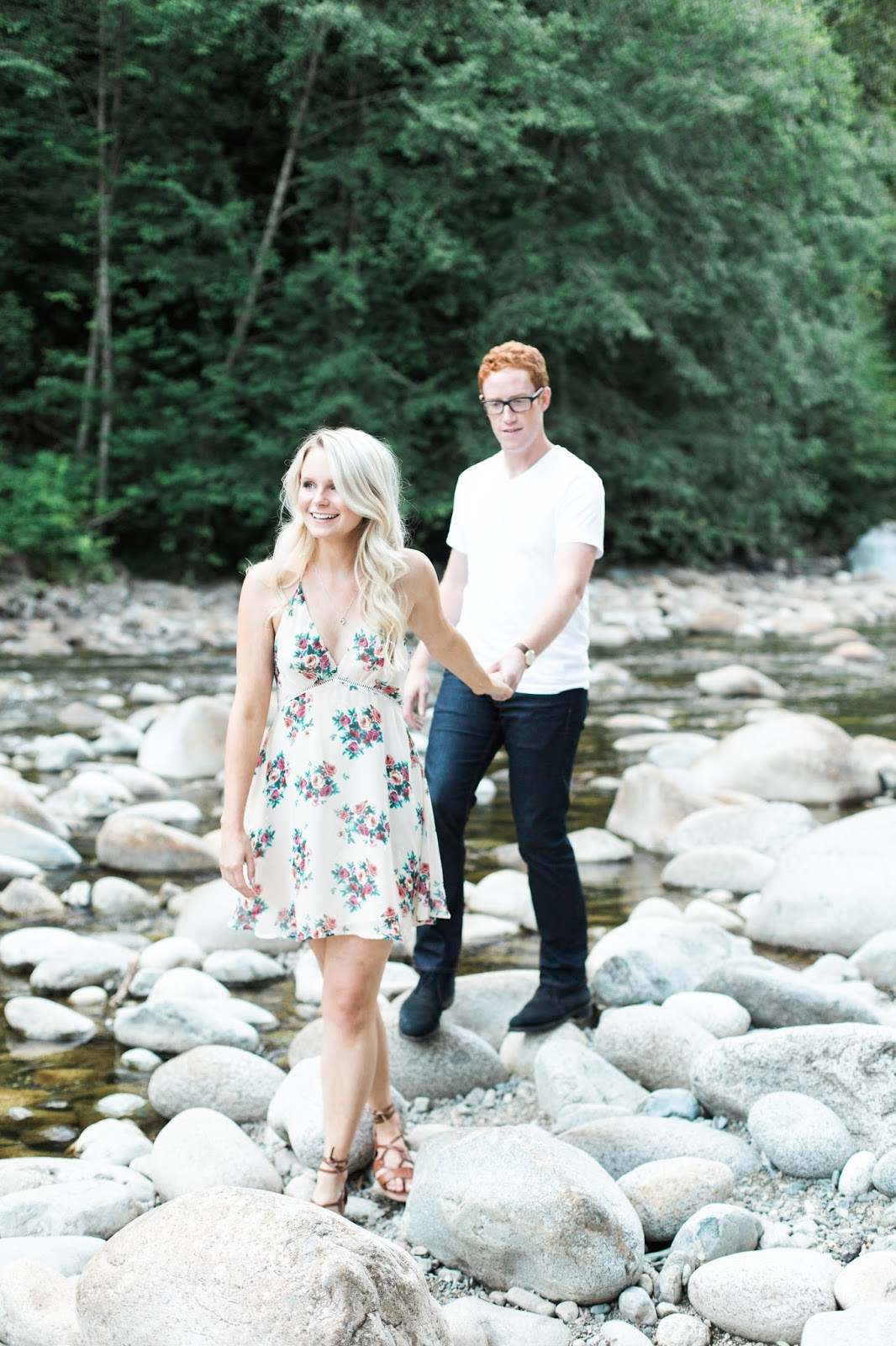 a blonde women with loose curly hair leads her fiancé through a creek in the summer, posing for engagement photos