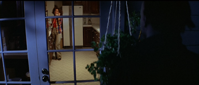 Annie (Nancy Loomis) does not realize Michael Myers is lurking outside in HALLOWEEN (1978).
