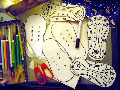 Inicio del proceso de creación de zapatos de cartón: siluetas blancas pintadas con rotulador negro, junto a tijeras y rotuladores de colores. Fotografía ©Selene Garrido Guil