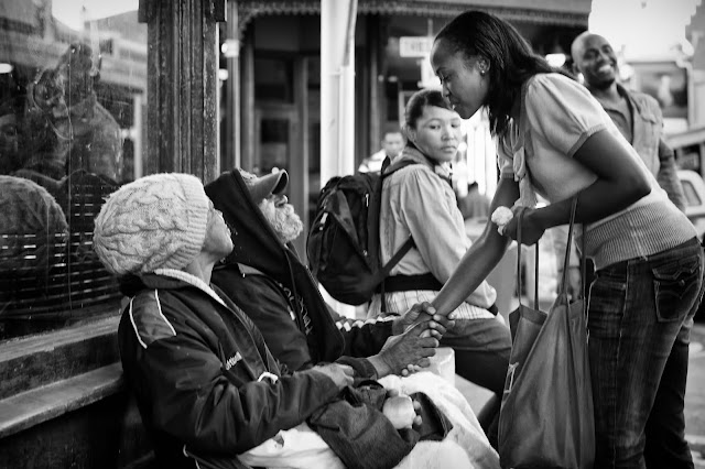 A young woman gives food to two homeless people - one of whom clasps her hand
