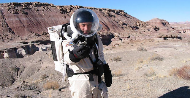 Dr. R.Zubrin with dinosaur fossil during EVA near MDRS in 2002. Credit: Mars Society
