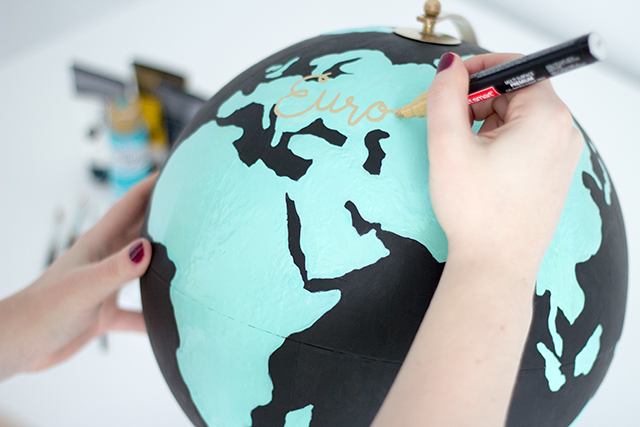 Use a gold paint pen to write continent names on your DIY Anthropologie inspired wanderlust globe.