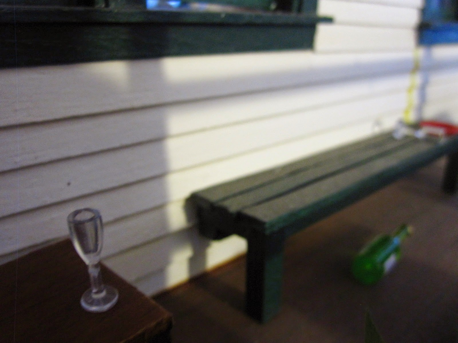 Modern dolls' house miniature verandah with a wine bottle, plate and wine glasses strewn around.