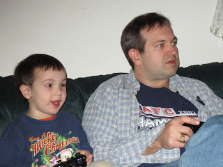 Son & father playing Xbox on the couch