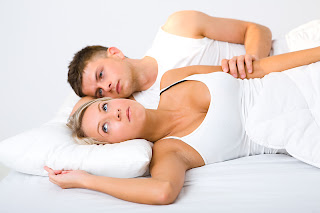 Couple lying in bed awake