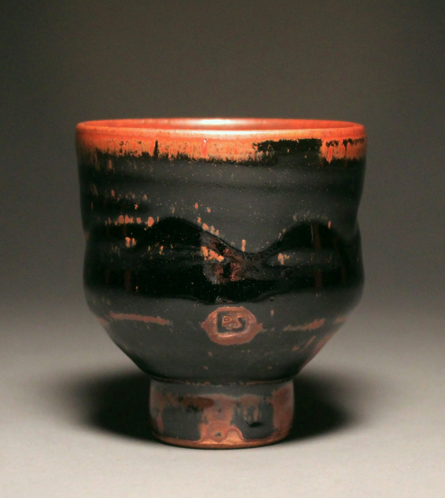 This is a dark glazed cup made from stoneware clay. The glaze is temmoku and has a tall foot.