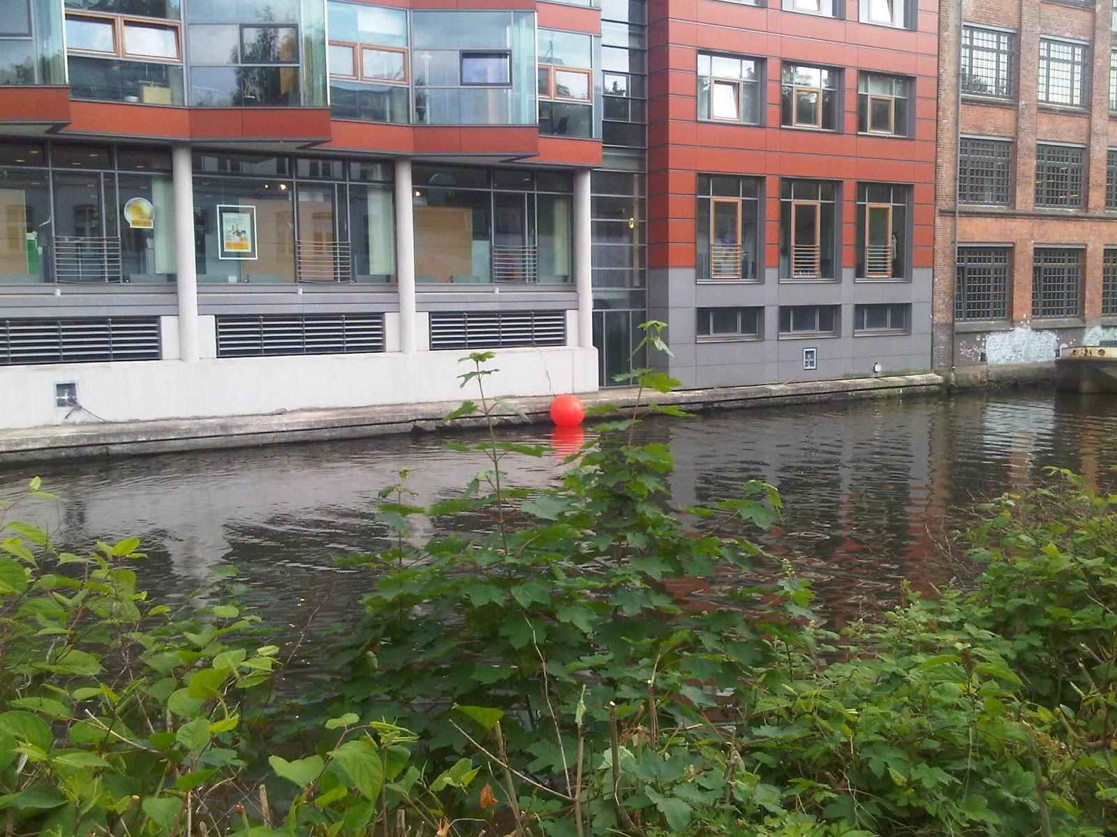 Goldbeckkanal mit neuem und altem Gebäude. Rote Boje im Wasser am Steg.