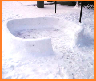 The first couple of feet of an igloo that was never completed, surrounded by snow.